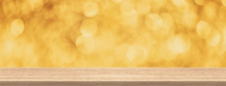 Wood table top in front of gold glitter bokeh abstract background for product and display montage banner size.