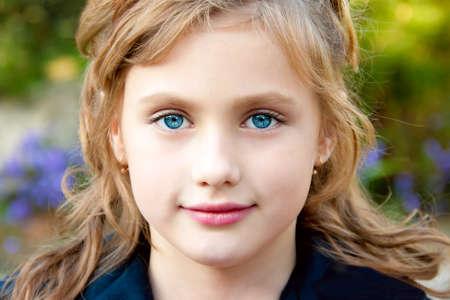 jolie petite fille: Portrait d'une jolie petite fille sur le fond de la nature.