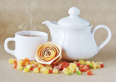 Background with white teapot and a cup of tea. Stock Photo