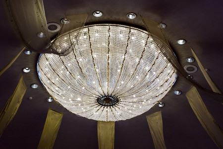 shining chandelier hanging on a ceiling in hotel photo