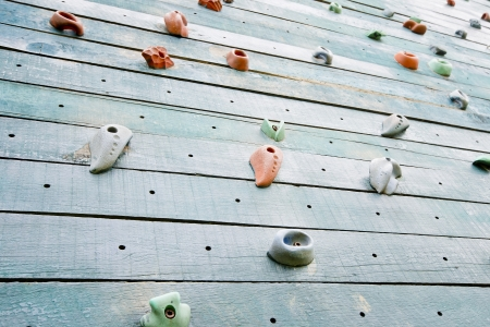 Grunge surface of an artificial rock climbing wall with toe and hand hold studs  photo