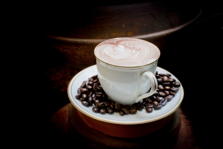 Latte art, coffee in coffee beans and Asian pottery background photo