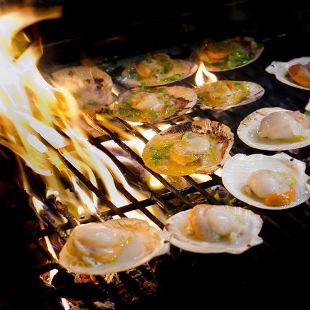 Gegrillte Jakobsmuscheln garniert mit Butter, Knoblauch und Petersilie auf lodernden Grill