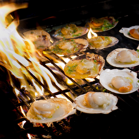 Grilled scallops topped with butter, garlic and parsley on flaming grill  Banque d'images