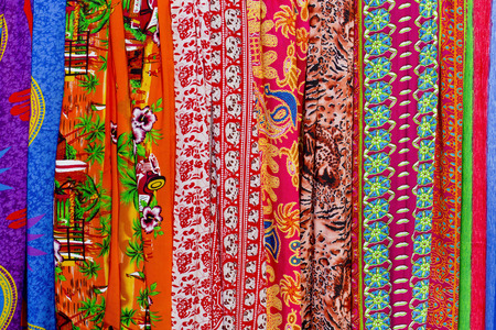 Rows of colourful silk scarfs hanging at a market stall in Thailand