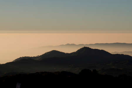 ridgeline: layers of mountains and fog at sunrise Stock Photo