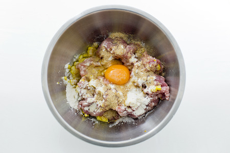 Minced meat,corns, eggs and flour in stainless steel bowl photo