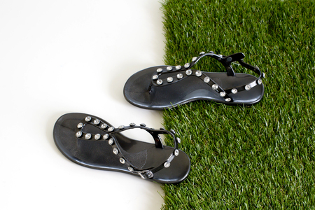 Sandals with rhinestones on green grass  View from above  Isolate on white  photo
