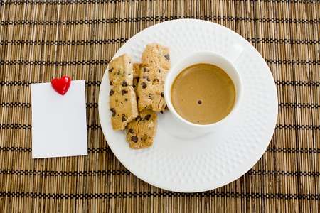 a cup of white coffee and chocolate chip cookies with notepad and smile magnet over a wooden table  photo
