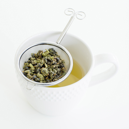 tea strainer: Herbal tea in a glass cup, metal sieve with dry herbal tea on a white background