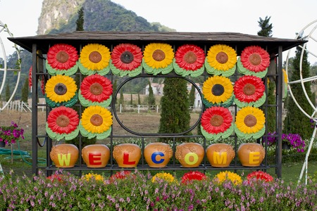 fench: welcome sign in the garden with colorful flowers on the background