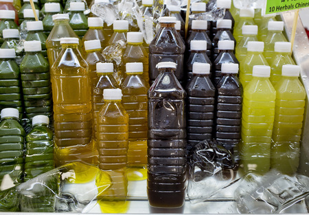 Assortment of cold tropical fruit juice in bottles. photo