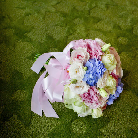 Bouquet of blooming colorful flowers on a green carpet background. photo