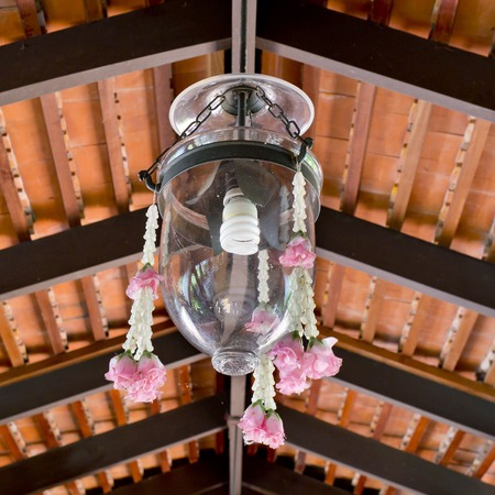 lamp shade: Thai style a glass lamp shade with flower garland decoration hanging in home.