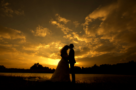 Het silhouet van bruidspaar met de zonsondergang