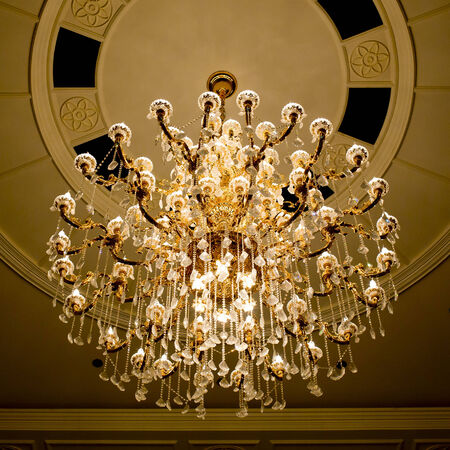 classical crystal chandelier hanging on beautiful ceiling photo