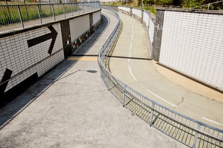 metal handrail: walkway with a metal handrail.