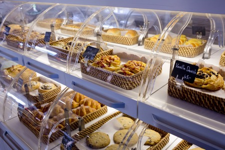 Variety of baked products in baskets with bread name and price on black small sign board at a bakery shop
