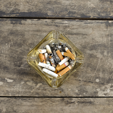 ashtray full of butt cigarettes on wooden background Stock Photo