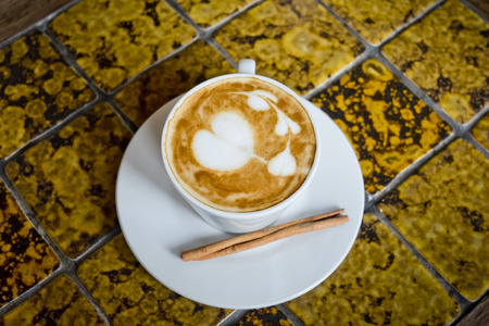 cafe latte: A cup of cafe latte and Cinnamon stick.