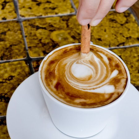 stirred: A coffee cup Latte being stirred by Cinnamon sticks. Stock Photo