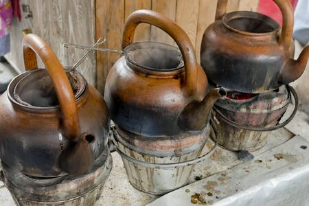 primus: baked clay kettle with hot water on stove.