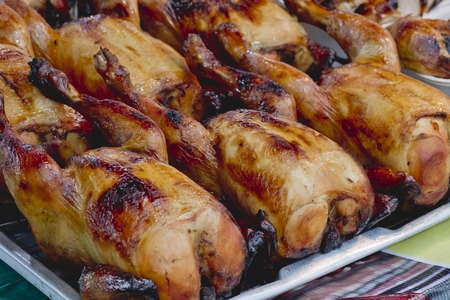 Many Roasted chickens served on stainless tray.