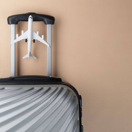 Flat lay grey suitcase with mini airplane on pastel background. travel concept - Image