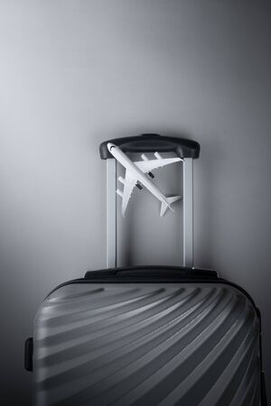 Flat lay grey suitcase with mini airplane on grey background. travel concept - Image