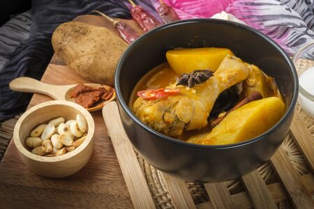 Massaman Curry With Chicken and Thai herbs with wood background