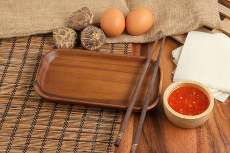 Empty plates with chopsticks by wooden styles. Space for text. T