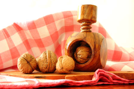 military press: Walnuts and antique nutcracker Stock Photo