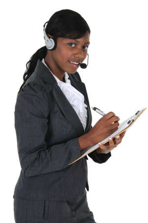A attractive business woman wearing a headset and writing on a clipboard, isolated on a solid white background.