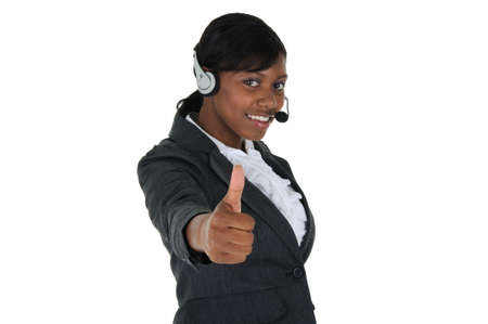 A attractive business woman wearing a headset and and giving the thumbs up, isolated on a solid white background. 写真素材