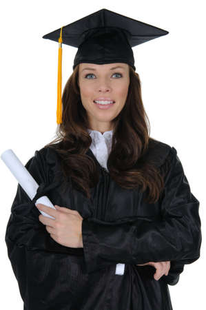 graduating: A happy female college graduate with arms crossed holding a diploma, isolated on a solid white background. Stock Photo