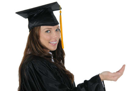A attractive woman graduate wearing a black cap and gown with gold tassel, holding out a open hand. Isolated on a solid white background. Foto de archivo