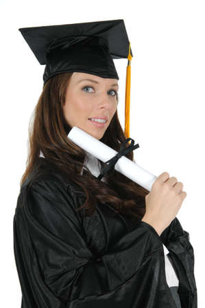 A attractive woman graduate wearing a black cap and gown with gold tassel, excited about her bright future. Isolated on a solid white background.