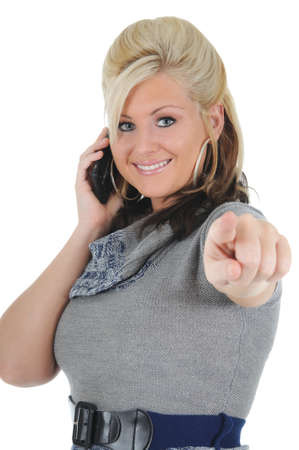 A attractive young blonde woman using her smart phone, and pointing at the camera. Isolated on a solid white background.  Foto de archivo