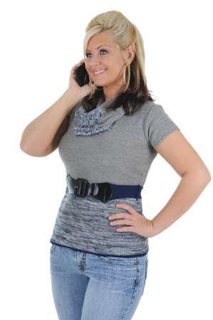 Una atractiva joven rubia teniendo una conversación en su teléfono inteligente. Aislado en un fondo blanco sólido. Foto de archivo - 10282352