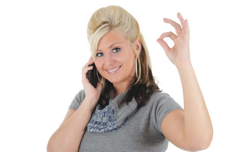A attractive young blonde woman on her smart phone, displaying the okay sign. Isolated on a solid white background.  Foto de archivo