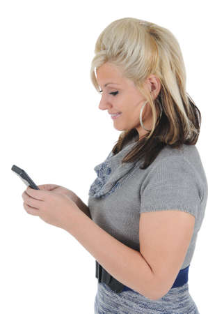 A attractive young blonde woman sending a text message on her smart phone. Isolated on a solid white background.  Stock Photo