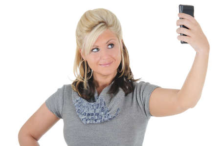 A attractive young blonde woman taking a photo of herself using her smart phone. Isolated on a solid white background.