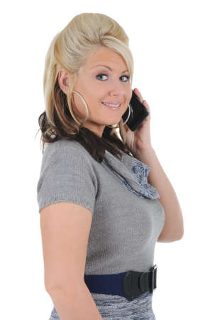 A attractive young blonde woman having a conversation on her smart phone. Isolated on a solid white background.  Foto de archivo
