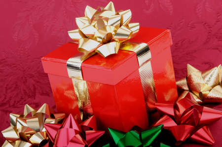 A red Christmas gift box with gold ribbons surrounded by colorful bows.