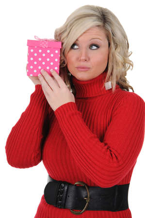 A young woman trying to guess whats inside a pink gift box. Valentines Day concept. Isolated on a solid white background.