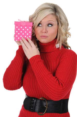 Una joven mujer tratando de adivinar lo que hay dentro de una caja de regalo de color rosa. Concepto de Día de San Valentín. Aislado en un fondo blanco sólido. Foto de archivo - 11976939