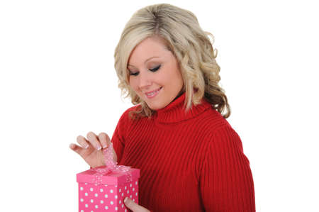 A lovely young woman opening a pink gift box. Valentines Day concept. Isolated on a solid white background.