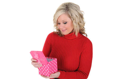 A lovely young woman opening a pink gift box. Valentine's Day concept. Isolated on a solid white background.  Foto de archivo