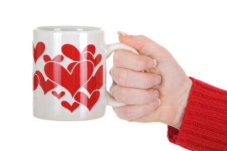 A close up of a female hand holding a cup with red hearts. A great valentine concept. Isolated on a solid white background.  photo