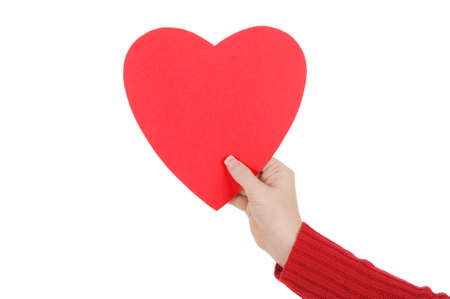 A close up of a female hand holding a red paper heart. Love and romance concept. Isolated on a solid white background.  Foto de archivo